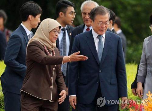 公式歓迎式でハリマ・ヤコブ大統領の案内を受ける文大統領(右)=12日、シンガポール(聯合ニュース)