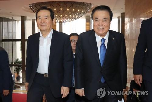 国会本会議に出席する文氏(右)。左は前国会議長の丁世均(チョン・セギュン)氏=13日、ソウル(聯合ニュース)
