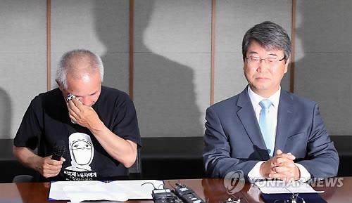合意文書の署名式で涙を流す遺族代表(左)=24日、ソウル(聯合ニュース)