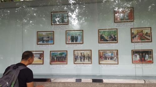 北朝鮮大使館の掲示板に、金委員長と韓米中首脳との各会談の写真が掲示された=29日、北京(聯合ニュース)