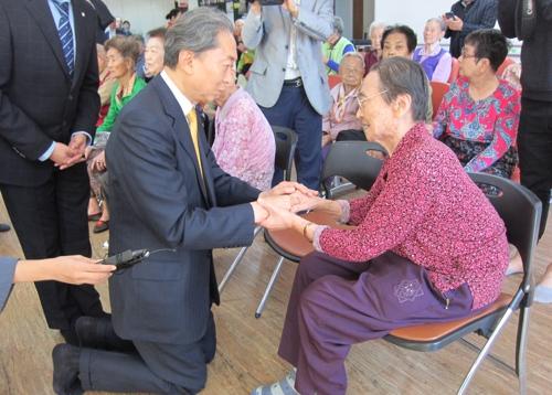 被爆者の女性の手を取り言葉をかける鳩山氏=3日、陜川(聯合ニュース)