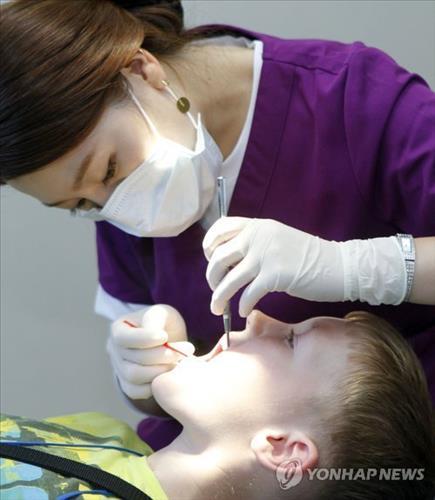 의사가 외국인 소년의 입을 면밀히 검사하고 있다.(사진)