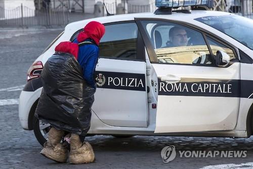 한 노숙 여성이 바티칸 성베드로 광장에서 경찰과 이야기하고 있다.[EPA=연합뉴스]