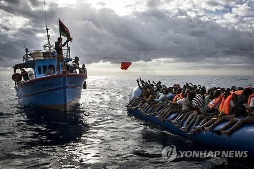 표류하는 고무보트 승선 난민들에 구명조끼를 던져주는 리비아 어선[EPA=연합뉴스]