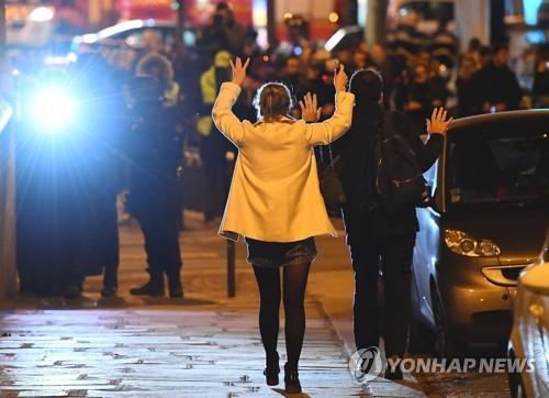 파리 샹젤리제 거리 테러 현장에서 손을 올리고 대피하는 시민들[AFP=연합뉴스]