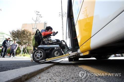 전동휠체어를 타고 저상버스에 오르는 장애인. [연합뉴스 자료사진]