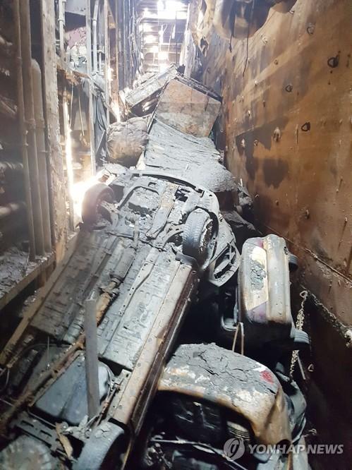 진흙 범벅인 승용차와 소형 트럭, 컨테이너들이 엉망으로 뒤엉킨 세월호 화물칸