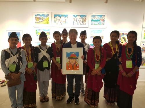 엄홍길 대장이 자신을 그린 그림을 들고 네팔 학생들과 기념촬영하고 있다.
