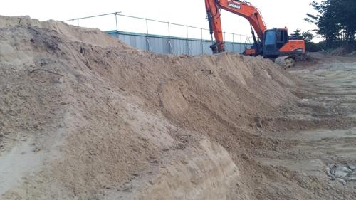 펜스를 치고 모래를 쌓아놓은 공사현장