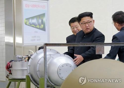 '핵탄두'를 둘러보는 북한 김정은 위원장(가운데)[연합뉴스 자료 사진]