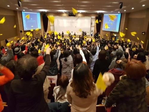 노랑 종이비행기를 접어 날리는 참가자들