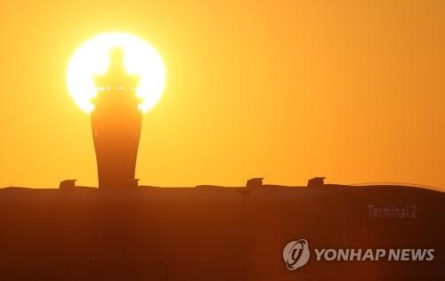 인천국제공항 제2여객터미널 관제탑 뒤로 해가 떠오르는 모습 [연합뉴스 자료사진]