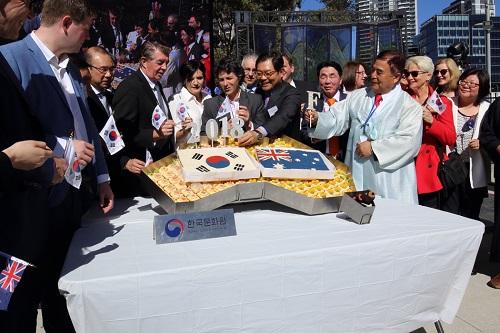호주 시드니 한민족축제에서 양국 인사 한국과 호주 깃발을 떡케이크에 꼿고 있다.