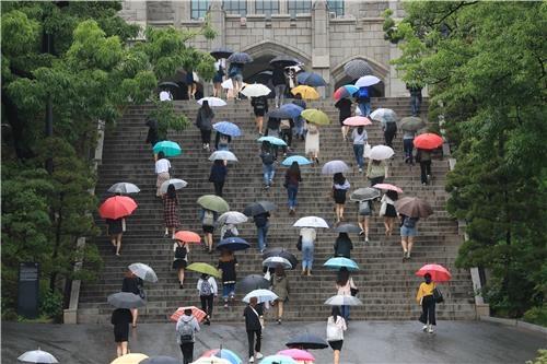 등굣길 학생들이 우산을 쓰고 계단을 오릅니다 / 서명곤