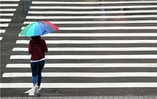 한 시민이 우산을 쓰고 출근합니다 /김인철