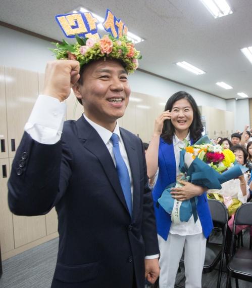 '만세'란 단어가 새겨진 월계관을 머리에 쓴 김승수 당선인