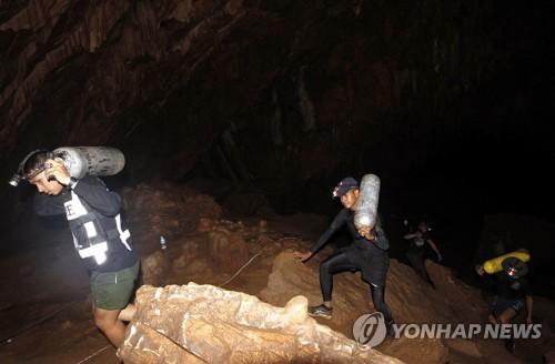 산소통 들고 동굴로 들어가는 잠수대원들[epa=연합뉴스]
