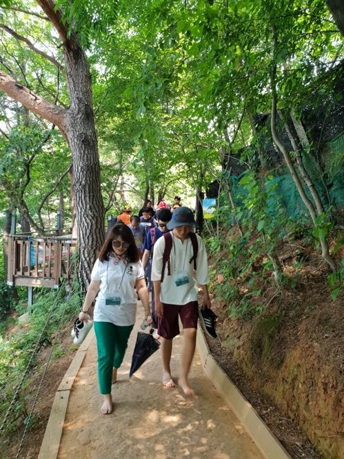 회동수원지 황토흙길 걷는 시민 [부산 금정구 제공]