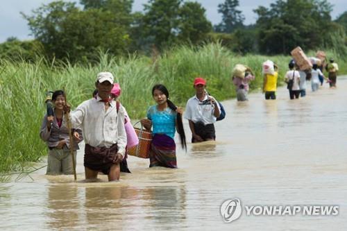 댐 사고 지역인 중부 바고의 타웅누에서 물속을 걸어가는 사람들[AFP=연합뉴스]
