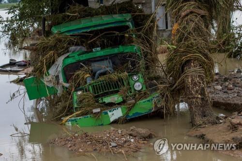 댐 사고에 따른 홍수로 떠내려가면서 부서진 트럭[AFP=연합뉴스]