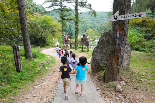 손잡고 공룡 수목원을 거니는 어린이들.
