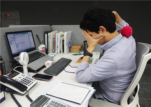 직장인이 사무실에서 셀프 마사지용품을 사용하는 모습