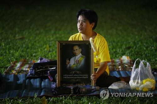 푸미폰 국왕 2주기 추모행사가 열리기를 기다리는 태국 여성[epa=연합뉴스]