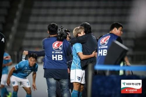 포항의 강상우가 경남전에서 골을 넣고 최순호 감독과 포옹하고 있다.