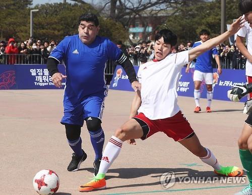 Diego Maradona (izq.) y el actor Ryu Jun-yeol (dcha.) durante un partido de futbito celebrado, el 14 de marzo del 2017, en una plaza frente al palacio de Hwaseong Haenggung, en Suwon, en la provincia de Gyeonggi.