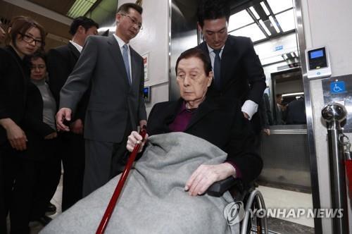 Shin Kyuk-ho llega al tribunal en silla de ruedas.