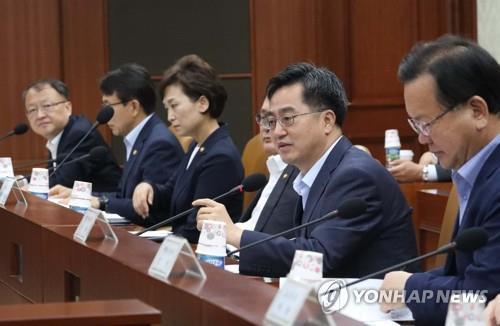 El ministro de Estrategia y Finanzas, Kim Dong-yeon (2º por la dcha.) en una reunión mantenida con los ministros relacionados con la economía el 16 de julio del 2017 en el complejo gubernamental de Sejong.