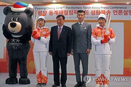 Lee Hee-beom (centro), presidente del Comité Organizador de PyeongChang para los Juegos Olímpicos y las Paralimpiadas de Invierno de 2018, posa, el 8 de septiembre de 2017, para una fotografía con Sean (segundo por la dcha.), un cantante surcoreano nombrado embajador honorario de las Paralimpiadas de Pyeongchang 2018, y voluntarios alzando la antorcha paraolímpica.