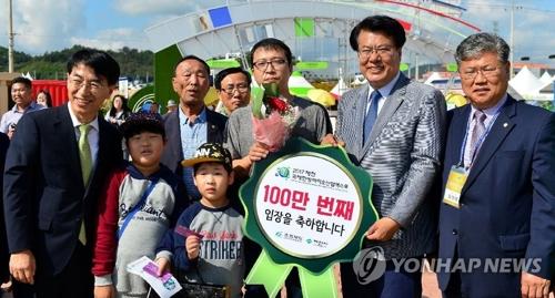 El visitante número 1.000.000 (centro) de la Exposición Mundial de Bioindustria, en Jecheon, y su familia, posan ante la cámara, el 8 de octubre de 2017, junto al alcalde de la ciudad, Lee Keun-kyu (segundo por la dcha.).