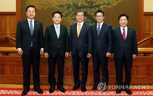 El presidente Moon Jae-in (centro), posa para la foto con legisladores de los partidos gubernamental y de la oposición, en la oficina presidencial Cheong Wa Dae, el 11 de octubre de 2017.