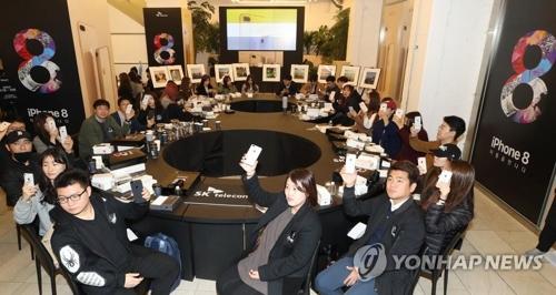 Las personas muestran sus iPhone 8 durante un evento de SK Telecom, en Seúl, por el lanzamiento del nuevo teléfono inteligente emblemático de Apple en el país.