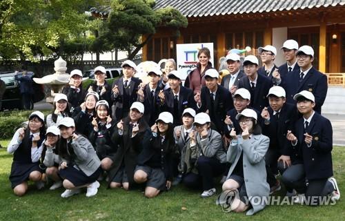 La primera dama de Estados Unidos, Melania Trump, se hace una foto, el 7 de noviembre de 2017, con estudiantes surcoreanos frente a la residencia del embajador de EE. UU., en Seúl.