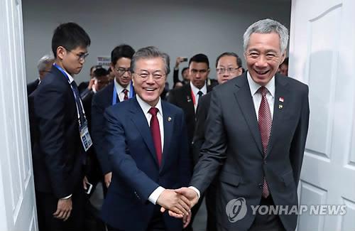 El presidente surcoreano, Moon Jae-in (centro), estrecha la mano del primer ministro de Singapur, Lee Hsien Loong (dcha.), antes de celebrar una cumbre bilateral, el 14 de noviembre de 2017, en Manila, Filipinas.