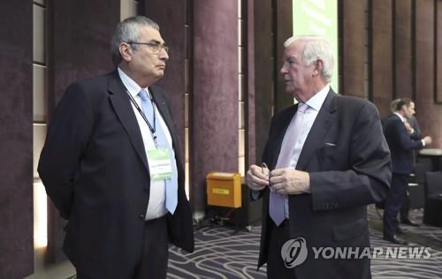 Ugur Erdener (izda.), vicepresidente del Comité Olímpico Internacional (COI), habla con Craig Reedie, presidente de la Agencia Mundial Antidopaje (AMA), antes de la reunión del Consejo de Fundación de la AMA, el 16 de noviembre de 2017 (AP - Yonhap)