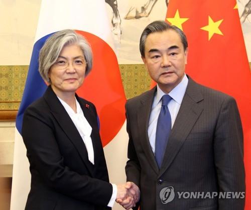 La ministra de Asuntos Exteriores de Corea del Sur, Kang Kyung-wha (izda.), estrecha la mano de su homólogo chino, Wang Yi, antes de sus conversaciones mantenidas, el 22 de noviembre de 2017, en Pekín.