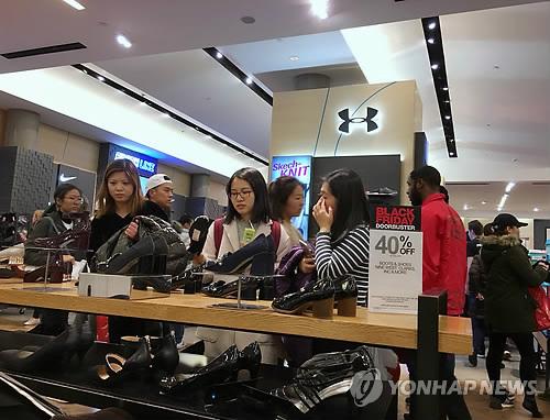 Los compradores observan los zapatos en una tienda en Nueva York, Estados Unidos, durante el período de rebajas por el Viernes Negro. (AP-Yonhap)