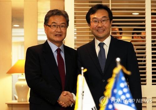 El jefe negociador nuclear surcoreano, Lee Do-hoon (dcha.), y su homólogo de Washington, Joseph Yun, se estrechan la mano en un encuentro para discutir temas norcoreanos, celebrado, el 17 de noviembre del 2017, en la isla surcoreana de Jeju. (Foto de archivo)