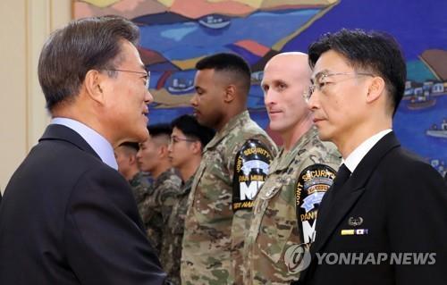 El presidente surcoreano, Moon Jae-in (izq.), saluda al doctor Lee Cook-jong del Hospital Universitario de Ajou, en un evento celebrado el 1 de diciembre de 2017, invitando a los soldados y a aquellos que ayudaron en la recuperación de un soldado norcoreano que desertó al Sur recibiendo diversas balas durante el proceso.