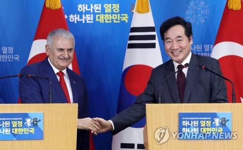 El primer ministro surcoreano, Lee Nak-yon (dcha.), da la mano a su homólogo turco, Binali Yildirim, después de una conferencia de prensa conjunta, celebrada, el 6 de diciembre de 2017, en Seúl.