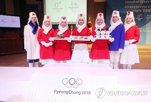 Modelos surcoreanos visten los trajes para las ceremonias de victoria de los Juegos Olímpicos y Paralímpicos Invernales de PyeongChang 2018, en el podio olímpico, el 27 de diciembre de 2017.