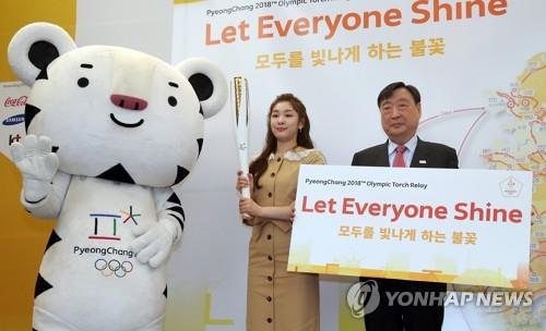 Lee Hee-beom y la excampeona olímpica de patinaje artístico, Kim Yu-na, posan ante la cámara durante un evento para los medios de comunicación para el relevo de la antorcha, celebrado, el 17 de abril de 2017, en Seúl.