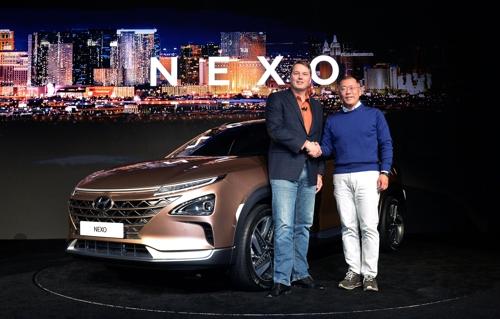 En la imagen, proporcionada por Hyundai Motor, se muestra al vicepresidente de la firma, Chung Eui-sun (dcha.), y el CEO de Aurora Innovation, Chris Urmson, posando ante la cámara, el 8 de enero de 2017 (hora local), en un centro de convenciones de Las Vegas, donde desvelaron el vehículo utilitario deportivo de celdas de combustible de hidrógeno llamado Nexo, un día antes de la inauguración del Salón de Electrodomésticos (CES) 2018.