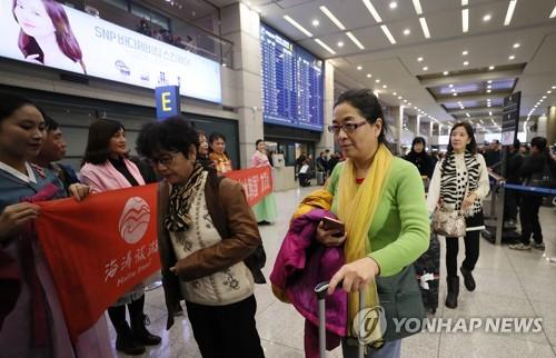 Un grupo de turistas chinos llega a Corea del Sur, el 2 de diciembre de 2017, a través del Aeropuerto Internacional de Incheon, al oeste de Seúl.