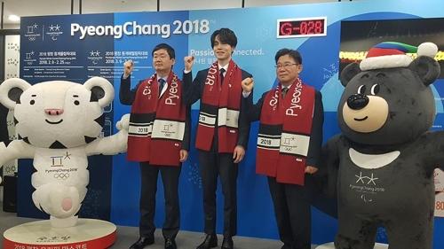 El actor surcoreano Lee Dong-wook (centro) posa ante la cámara durante la ceremonia de nombramiento como embajador honorario de los JJ. OO. de Invierno de PyeongChang, organizada,  el 12 de enero de 2018, en el centro de Seúl.