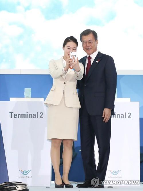 El 12 de enero de 2018, el presidente, Moon Jae-in, posa para una foto con una empleada del aeropuerto en la ceremonia de apertura de la segunda terminal de pasajeros del Aeropuerto Internacional de Incheon.