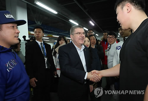 """Thomas Bach (centro) da la mano al piloto surcoreano de """"bobsleigh"""" Won Yun-jong, durante su visita a la sala de pesas del equipo nacional de """"bobsleigh"""", realizada, el 30 de enero de 2018, en PyeongChang, en la provincia de Gangwon."""